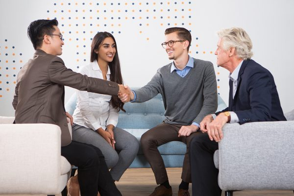 Smiling young business men shaking hands. They and their partners are sitting in armchairs and sofa in lounge.